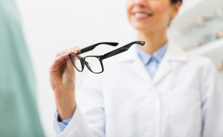 health care decisions: health care, people, eyesight and vision concept - close up of smiling woman optician holding glasses at optics store Stock Photo