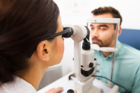 optical equipment: health care, medicine, people, eyesight and technology concept - close up of optometrist with slit lamp checking patient vision at eye clinic or optics store
