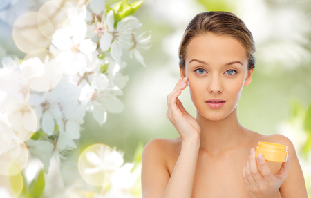 cosmeticos: beauty, people, cosmetics, skincare and cosmetics concept - young woman applying cream to her face over green natural background with cherry blossom