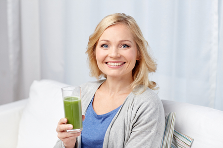 woman diet: healthy eating, vegetarian food, dieting, detox and people concept - smiling middle aged woman drinking green fresh vegetable juice or smoothie from glass at home