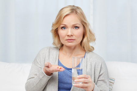 take a: medicine, health care and people concept - middle aged woman with medicine and water glass at home
