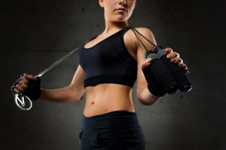 saltar la cuerda: deporte, gimnasio, entrenamiento, resistencia y concepto de la gente - cerca de la mujer joven deportiva con una cuerda de saltar