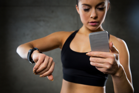 sport fitness: sport, fitness, technology and people concept - close up of young woman with heart-rate or smart watch and smartphone in gym Stock Photo