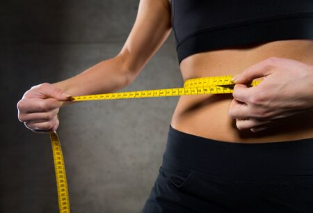 hands on waist: sport, fitness, weight loss, diet and people concept - close up of woman measuring waist size by tape in gym