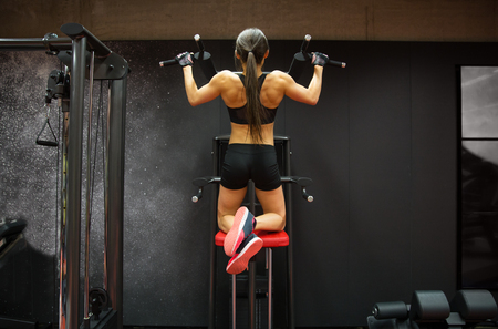 pull up: sport, fitness, lifestyle and people concept - woman exercising and doing pull-ups in gym from back Stock Photo