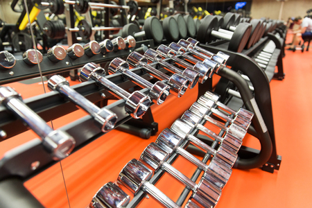 fitness, sport, exercising, weightlifting and bodybuilding concept - close up of dumbbells and sports equipment in gym Stock Photo