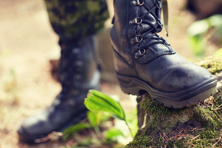work boots: war, hiking, army and people concept - close up of soldier feet in army boots in forest