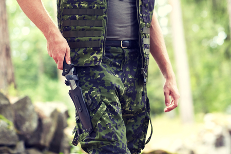 young knife: war, army, cold steel arms and people concept - close up of young soldier, ranger or hunter hands taking out knife in forest