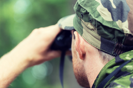 observing: hunting, war, army and people concept - close up of young soldier, ranger or hunter with binocular observing forest Stock Photo