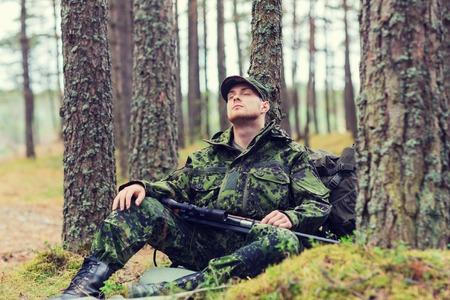 cazador: la caza, la guerra, el ejército y el pueblo concepto - joven soldado, guardabosques o un cazador con el arma sentarse y dormir en el bosque