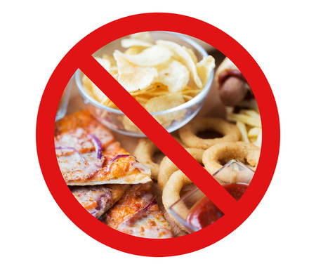 fattening: fast food, low carb diet, fattening and unhealthy eating concept - close up of pizza, potato chips and other snacks behind no symbol or circle-backslash prohibition sign
