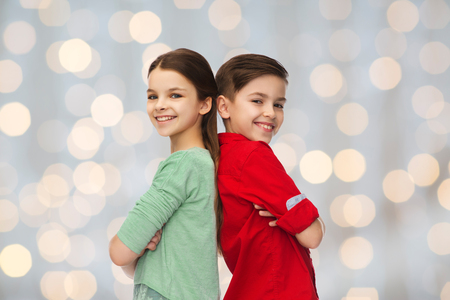 personas de pie: childhood, fashion and people concept - happy smiling boy and girl standing back to back over holidays lights background Foto de archivo