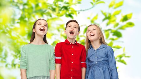 natural looking: childhood, summer, emotion, friendship and people concept - happy amazed boy and girls looking up with open mouths over green natural background Stock Photo