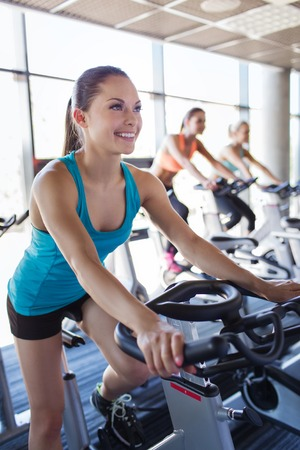 fitness gym: sport, fitness, lifestyle, equipment and people concept - group of women riding on exercise bike in gym