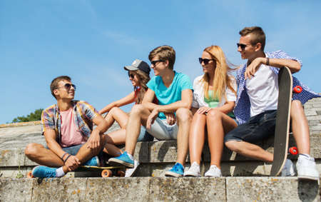 people, leisure and sport concept - group of happy teenage friends with longboard talking on city street Stock Photo