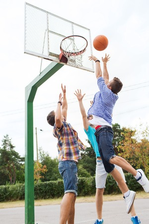 youth group: summer vacation, sport, games and friendship concept - group of happy teenage friends playing basketball outdoors