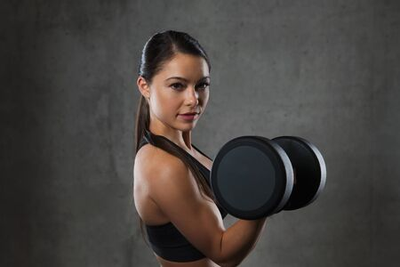 bicep: fitness, sport, exercising, training and people concept - young woman flexing muscles with dumbbells in gym