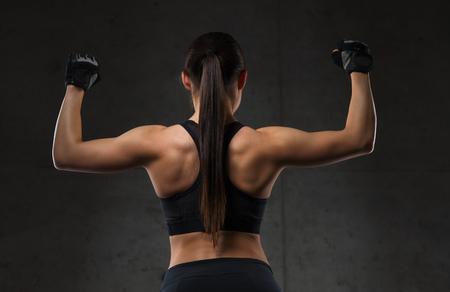 mujeres de espalda: deporte, fitness, culturismo, levantamiento de pesas y el concepto de la gente - Mujer que dobla pequeños músculos en el gimnasio