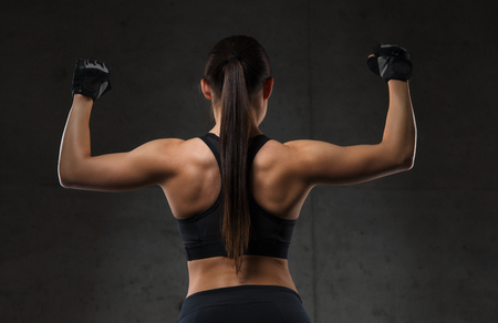 mujeres de espalda: sport, fitness, bodybuilding, weightlifting and people concept - young woman flexing muscles in gym