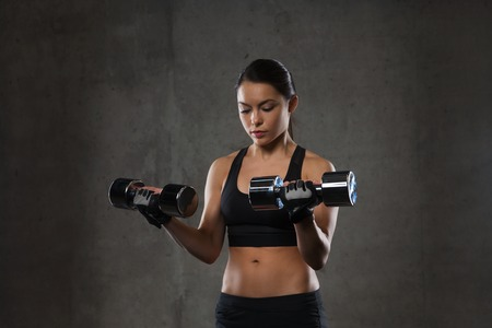 weightlifting gloves: fitness, sport, exercising, training and people concept - young woman flexing muscles with dumbbells in gym