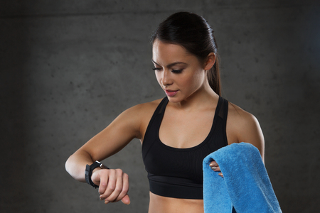 sport fitness: sport, fitness, technology and people concept - young woman with heart-rate watch and towel in gym