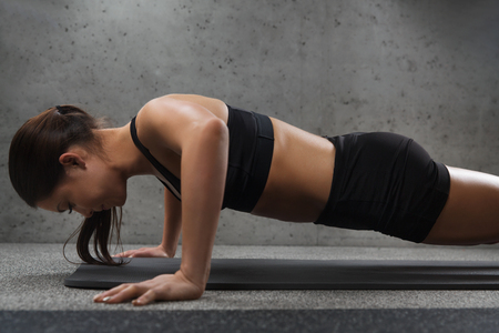 push ups: fitness, sport, people and exercising concept - woman doing push-ups in gym