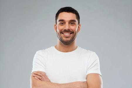 эмоции и люди концепции - счастливый улыбающийся молодой человек со скрещенными руками на сером фоне