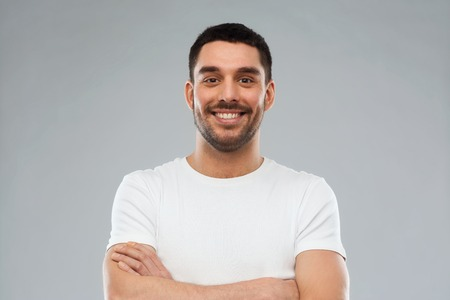 young adults: emotion and people concept - happy smiling young man with crossed arms over gray background