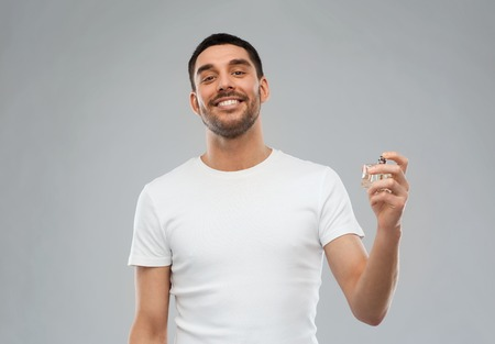 perfumery concept: perfumery, beauty and people concept - happy smiling young man with male perfume over gray background Stock Photo