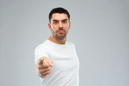 insult: emotion, gesture and people concept - angry man pointing finger to you over gray background