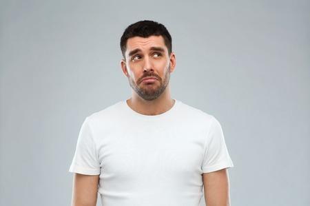 emotie, droefheid en mensen concept - ongelukkige jonge man over grijze achtergrond