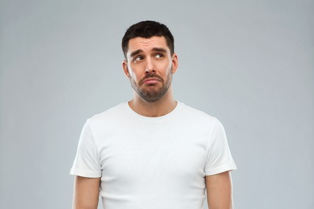 man sad: emotion, sadness and people concept - unhappy young man over gray background Stock Photo