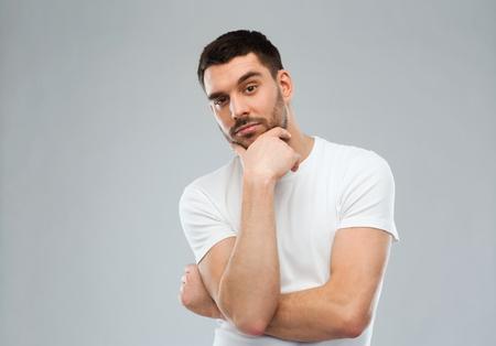 hombre pensando: duda, la expresión y el concepto de la gente - hombre de pensamiento sobre fondo gris