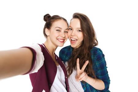 young schoolgirl: people, friends, teens and friendship concept - happy smiling pretty teenage girls taking selfie and showing peace sign
