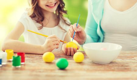 familia cristiana: Pascua, familia, día de fiesta, la gente y concepto de infancia - Primer plano de niña feliz y madre con pinceles para colorear los huevos de Pascua sobre fondo de las luces