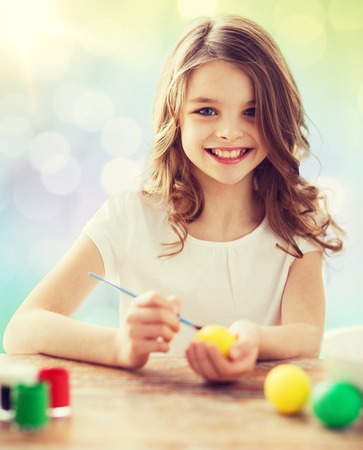 brush painting: easter, holiday and child concept - happy girl with brush coloring easter eggs over lights background