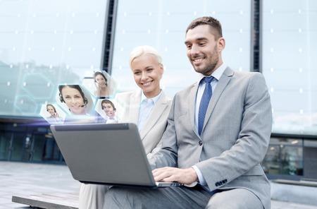 бизнес, коммуникации, технологии и люди концепции - улыбающиеся люди, делая видео звонок или конференцию с ноутбуком на улице города