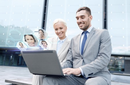 business, communication, technology and people concept - smiling businesspeople making video call or conference with laptop computer on city street Stock Photo