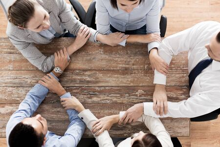team cooperation: business, people, cooperation and team work concept - close up of creative team sitting at table and holding hands in office