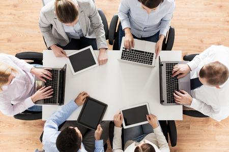 Concept d'entreprise, de personnes et de technologie - gros plan d'une équipe créative avec ordinateur portable et tablette pc assis à table au bureau Banque d'images