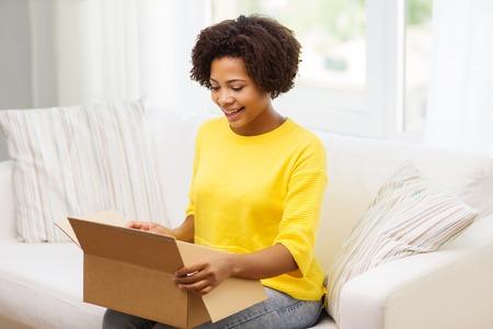 la gente, la entrega, el transporte y el concepto de servicio postal - feliz cuadro afroamericano apertura mujer joven de cartón o paquete en casa