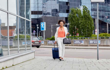 business centre: travel, business trip, people and tourism concept - happy young african american woman with travel bag walking down city street Stock Photo