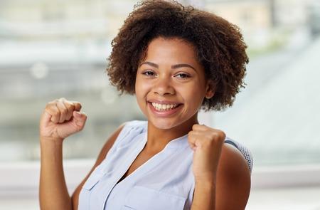 mensen, emoties, gebaar en succes concept - Gelukkig Afro-Amerikaanse jonge vrouw met opgeheven vuisten Stockfoto