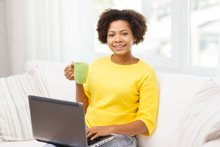 people, technology and leisure concept - happy african american young woman sitting on sofa with laptop computer and drinking tea from cup at home Stock Photo