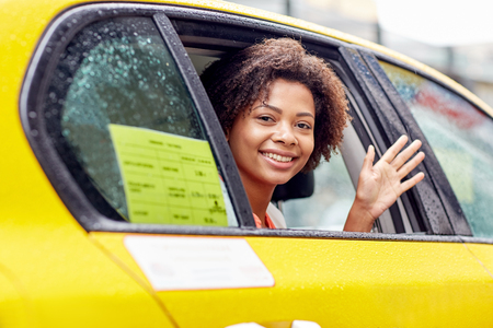 citylife: business trip, transportation, travel, gesture and people concept - young smiling african american woman driving in taxi and waving hand at city street