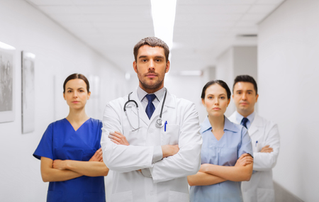 medics: clinic, profession, people, health care and medicine concept - group of medics or doctors at hospital corridor Stock Photo