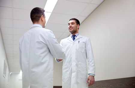 doctors smiling: clinic, profession, people, health care and medicine concept - smiling doctors meeting and greeting by handshake at hospital corridor