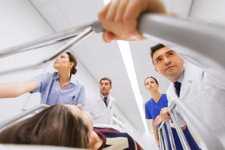beroep, mensen, gezondheidszorg, reanimatie en geneesmiddelen concept - groep van artsen of artsen dragen bewusteloze vrouw patiënt op ziekenhuisgurney tot de noodhulpdiensten Stockfoto