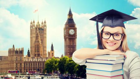 onderwijs, school, kennis en mensen concept - beeld van de gelukkige student meisje of vrouw in trencher cap met stapel boeken over huizen van het parlement in Londen stad achtergrond Stockfoto