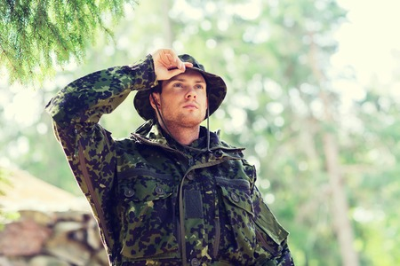 ranger: war, army and people concept - young soldier or ranger wearing military uniform in forest Stock Photo